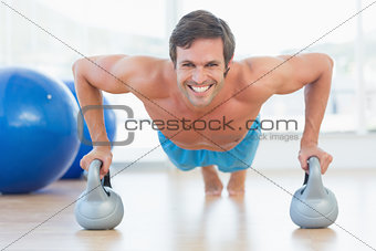 Portrait of a smiling young man doing push ups