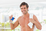 Shirtless young man with towel drinking water
