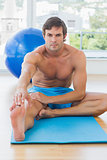 Sporty young man stretching hand to leg