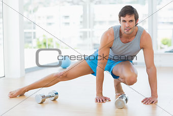 Sporty man doing stretching exercise in fitness studio