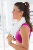 Side view of a smiling fit woman with towel in gym