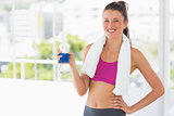 Fit woman with towel and water bottle in gym