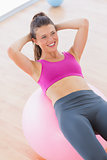 Smiling fit woman exercising on fitness ball at gym