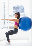 Fit young woman exercising with fitness ball