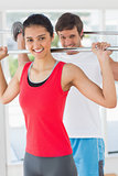 Fit young man and woman lifting barbells