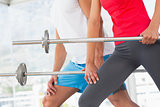 Mid section of fit young couple holding barbells