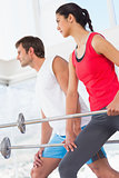 Fit young couple holding barbells in the gym