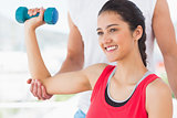 Instructor assisting smiling woman with dumbbell weight