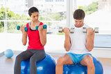 Couple lifting dumbbells while on fitness balls in gym