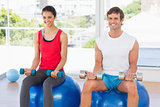 Couple lifting dumbbells while sitting on fitness balls in gym