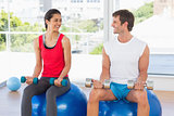 Happy couple lifting dumbbells while sitting on fitness balls in gym