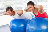 Fit couple exercising on fitness balls in gym