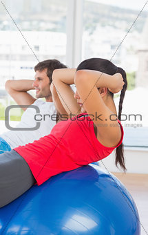 Fit young couple exercising on fitness balls in gym