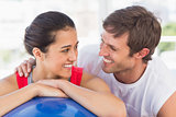 Closeup portrait of a smiling fit couple with exercise ball