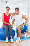 Portrait of a smiling fit couple with exercise ball at gym