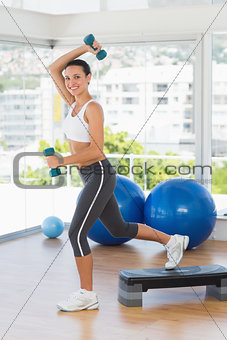 Fit young woman performing step aerobics exercise