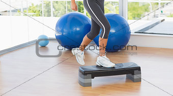 Low section of a fit woman performing step aerobics exercise