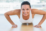 Smiling beautiful woman doing push ups in gym
