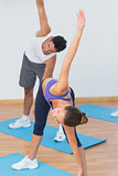 Sporty couple stretching hands at yoga class