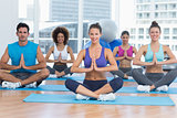 People in Namaste position smiling at fitness studio