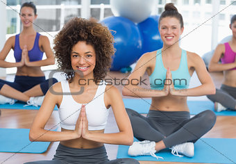 Smiling sporty young people in Namaste position
