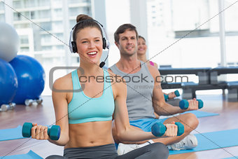 Fit people listening to music while lifting dumbbell weights