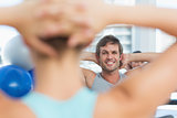 Smiling male with blurred people doing stretching exercises