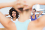 Smiling females with blurred trainer doing stretching exercises
