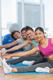 Sporty people stretching hands to legs in fitness studio