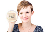 Pretty woman holding a tub of Organic Cream