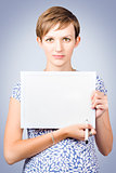 Serious woman holding white board with marker pen