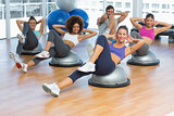 Portrait of cheerful fitness class doing pilates exercise