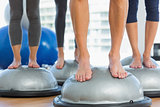 Low section of fit people standing on exercise equipment