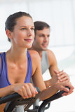 Smiling young couple working out at spinning class