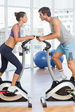 Side view of a couple working at spinning class in gym