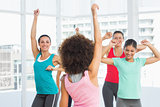 Cheerful fitness class and instructor doing pilates exercise