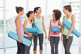 Fit smiling young women with exercise mats