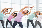 Smiling women doing pilate exercises in fitness studio
