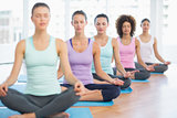 Sporty women in meditation pose with eyes closed at fitness studio