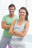 Portrait of a fit couple with arms crossed in exercise room