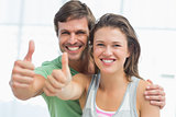 Portrait of a fit young couple gesturing thumbs up