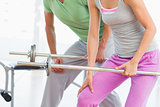 Mid section of fit couple holding barbells