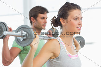 Fit young couple lifting barbells