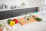 Vegetables with knife and chopping board on kitchen counter