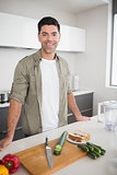 Man with vegetables and chopping board in kitchen