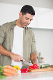 Smiling man chopping vegetables in the kitchen