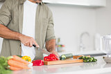 Mid section of a man chopping vegetables in kitchen