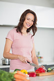 Smiling young woman chopping vegetables in kitchen