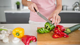 Mid section of a woman chopping vegetables in kitchen