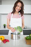 Smiling young woman with broccoli in kitchen